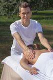 Man giving massage to young brunette outdoors Stock Photography