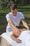 Man giving massage to young brunette outdoors. Sunny day Stock Photography