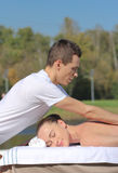 Man giving massage to young brunette outdoors Royalty Free Stock Images