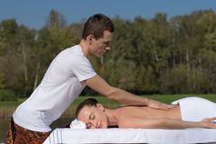 Man giving massage to young brunette outdoors. Sunny day Royalty Free Stock Photo