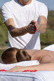 Man giving massage to young brunette outdoors. Sunny day Royalty Free Stock Image