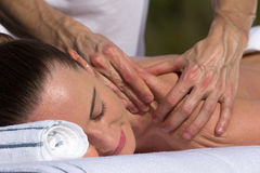 Man giving massage to young brunette outdoors. Sunny day Royalty Free Stock Photography