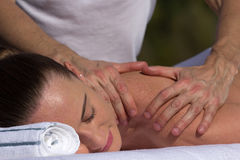 Man giving massage to young brunette outdoors. Sunny day Royalty Free Stock Photos