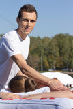 Man giving massage to young brunette outdoors. Sunny day Royalty Free Stock Images