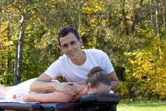 Man giving massage to young brunette outdoors Stock Photo