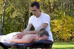 Man giving massage to young brunette outdoors. Sunny day Stock Photos