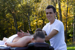 Man giving massage to young brunette outdoors Stock Photos