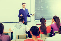 Man giving a math lesson. Serious men giving a math lesson in front of a group of students in the school stock image