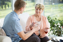 Man giving medications to older woman Stock Image