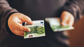 Man giving money cash. Male hands holding hundred euro banknote bill. Credit. Or lend concept Royalty Free Stock Images