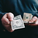 Man giving one us dollar banknote and holding cash in hands.Money credit concept Stock Images
