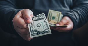 Man giving one us dollar banknote and holding cash in hands. Toned picture. Horizontal image royalty free stock image