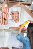 Man Giving Packed Sausages To Female Customer Royalty Free Stock Photos