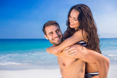 Man giving piggy back to his girlfriend at the beach Stock Photos