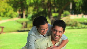Man giving a piggy back to his girlfriend. Man laughing while giving a piggy back to his girlfriend in a park stock footage