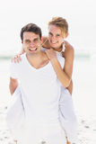 Man giving a piggy back to woman on the beach Royalty Free Stock Image