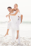 Man giving a piggy back to woman on the beach Royalty Free Stock Photos