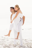 Man giving a piggy back to woman on the beach Stock Images