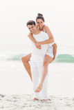 Man giving a piggy back to woman on the beach Royalty Free Stock Images