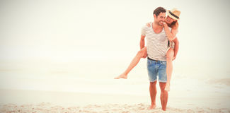 Man giving piggy back to woman. At sandy beach Stock Photography