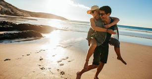 Man giving piggyback ride to girlfriend on beach. Happy young couple having fun on the seashore, enjoying summer holidays stock image