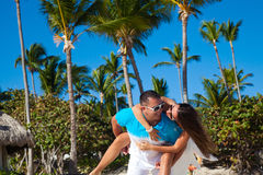 Man giving piggyback ride to girlfriend at the Caribbean beach Stock Photos