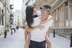Man giving piggyback ride to girlfriend, having stock photos