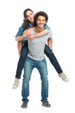 Man Giving Piggyback Ride To Her Girlfriend. Portrait Of Young Man Piggybacking Her Girlfriend Isolated On White Background Royalty Free Stock Photo