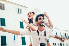 Man giving a piggyback ride to his girlfriend. Happiness lifestyle and tourism concepts stock photos