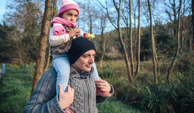 Man giving piggyback ride to little girl outdoors royalty free stock images