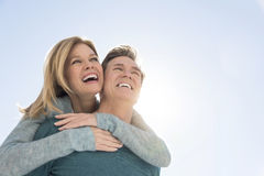 Man Giving Piggyback Ride To Woman Against Clear Sky Stock Photography