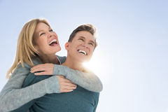 Man Giving Piggyback Ride To Woman Against Clear Sky Royalty Free Stock Photos