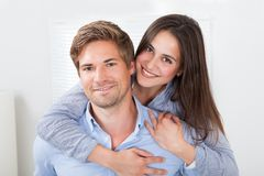 Man Giving Piggyback Ride To Woman At Home Stock Image