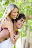 Man Giving Piggyback Ride to Woman in Park Royalty Free Stock Photo