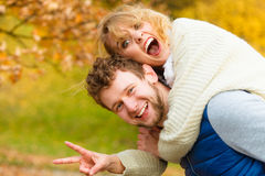 Man giving piggyback ride to woman in park Royalty Free Stock Photography