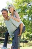 Man giving piggyback ride to woman Stock Image