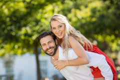 Man giving piggyback ride to woman Stock Photo