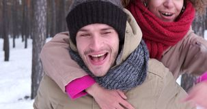 Man giving piggyback ride to woman in winter