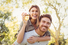 Man giving piggyback ride to women. In park on a sunny day Royalty Free Stock Photos
