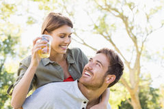 Man giving piggyback to woman while having glass of beer Stock Photos