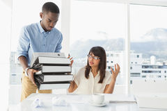 Man giving pile of files to his exasperated colleague. In the office royalty free stock photo
