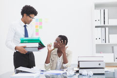 Man giving pile of files to his irritated colleague Stock Image