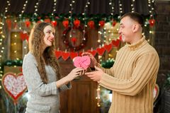 Man giving present to his girlfriend. In love couple celebrate valentine`s day. girl with tenderness looking at man, smiling and enjoy present Stock Photo