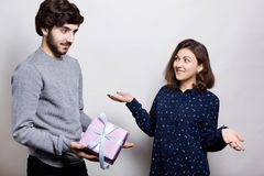 Man giving a present to his girlfriend. Romantic surprise, woman receives a gift from her boyfriend. Woman in love surprised looki stock photo