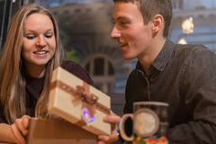 Man giving a present to his girlfriend. Romantic surprise. Women receives a gift from her boyfriend Stock Photo