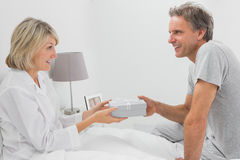Man giving present to his smiling partner Royalty Free Stock Photo