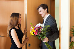 Man giving present to his young wife. At home door Stock Images