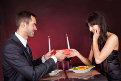 Man giving present to a woman in restaurant Stock Images