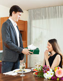 Man giving present to woman during romantic dinner Stock Photography
