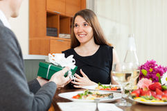 Man giving present to woman during romantic dinner Stock Images